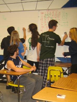 Seniors Elliot Salzberg, Eric Dennis, Alex Warren, Kirkland Boyle, Henry Powers, and Isabel Formby make full use of whiteboard space to solve the problem