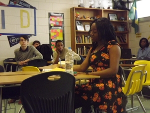 Dionna writes story ideas while the rest of the staff listens intently